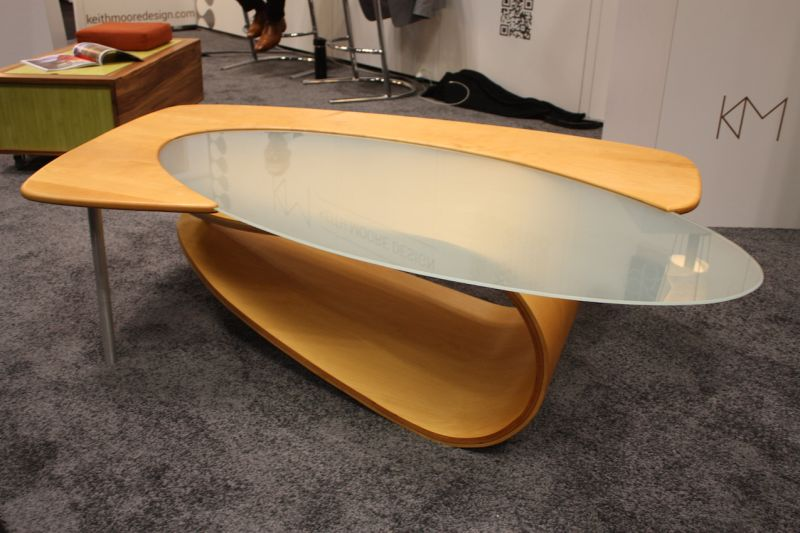 "The ""Fling"" coffee table by Keith Moore Designs is modern and futuristic with a soft edge. The curvy wood and oval frosted glass keep the piece from being too cold."