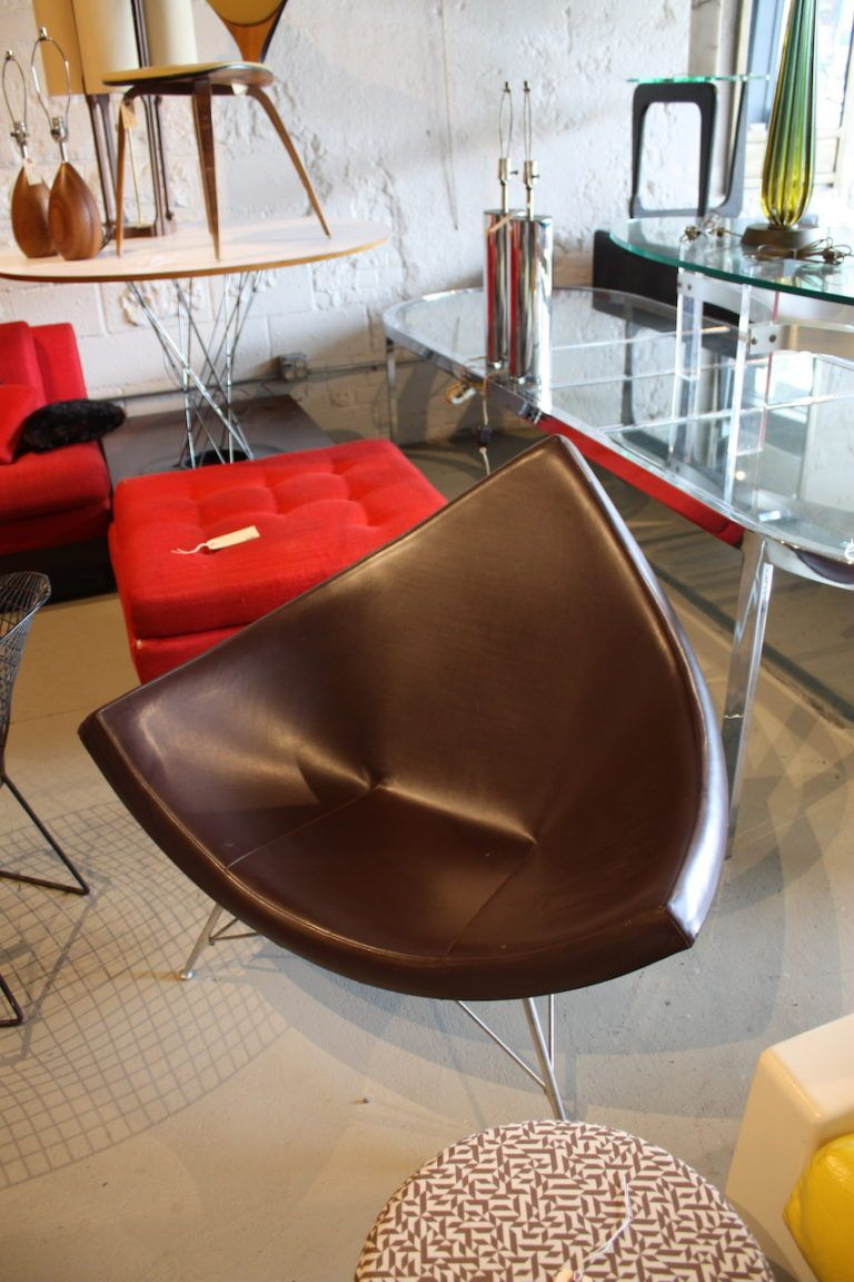"George Nelson's 1958 ""Coconut"" Chair is a winner for just about any space. Its triangular fiberglass body is formed into a cupped shape, cushioned and upholstered leather. The chair has three tubular aluminum legs."