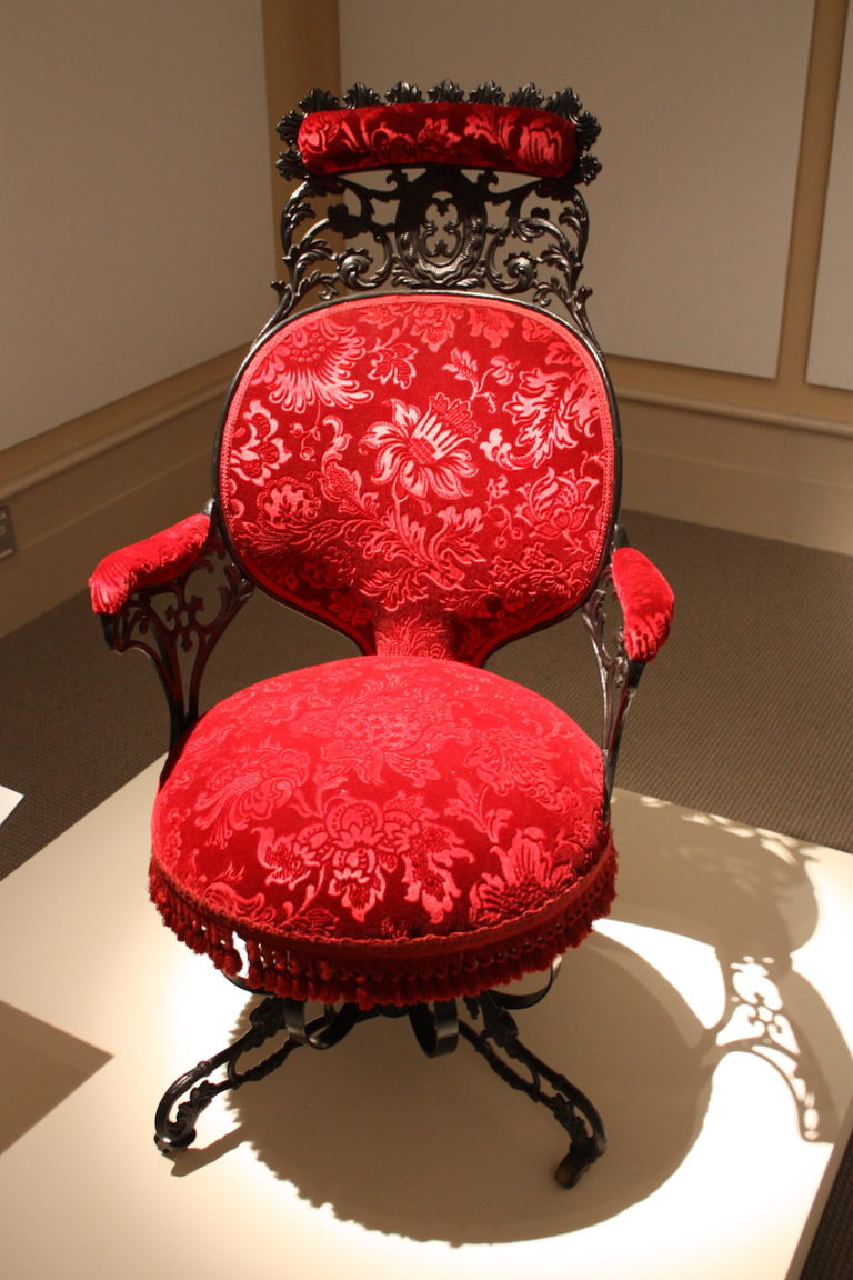 The armchair is fashioned from cast iron, wood, sheet metal, velvet, and faux rosewood graining.