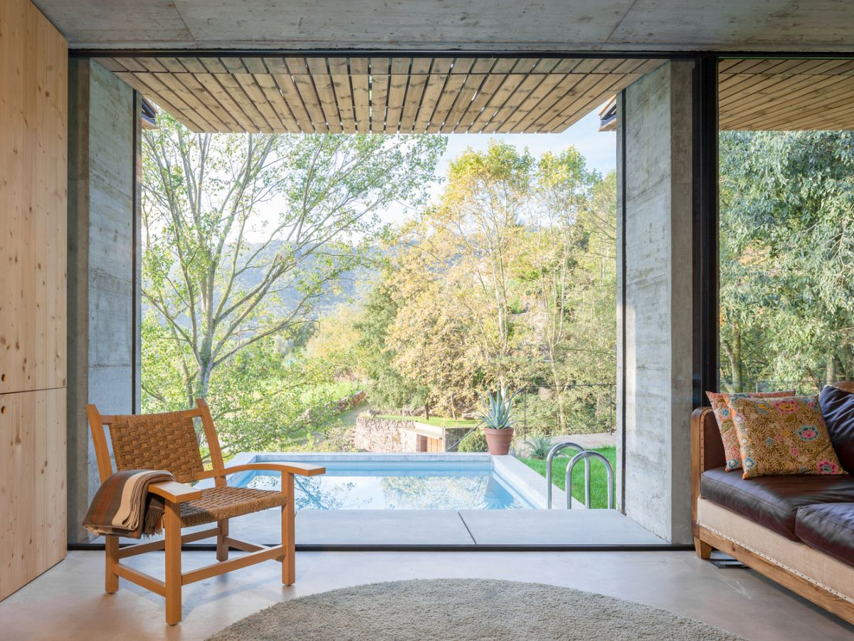 The full-height window overlooks the swimming pool and the beautiful valley in the distance